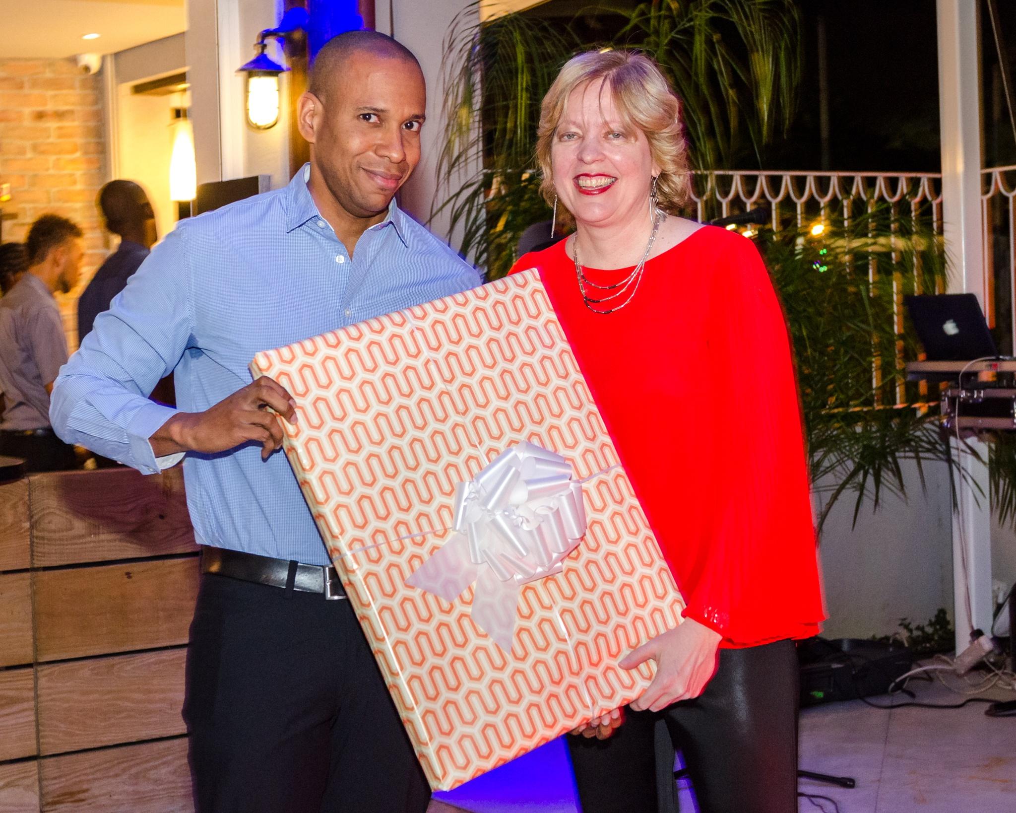 Anya Schnoor, Scotiabank's Head Caribbean South and East, presents David Noel's farewell gift - original artwork from his favorite artist